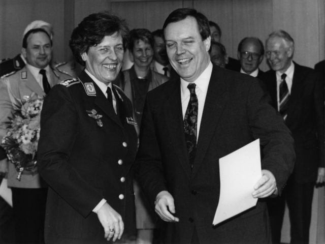 © dpa, Tim Brakemeier, Bonn, 25.3.94: Federal Defense Minister Volker Rühe (r) hands Verena von Weymarn the certificate of promotion to the general.